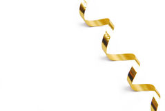 Golden confetti serpentine ribbon isolated on white Royalty Free Stock Photography