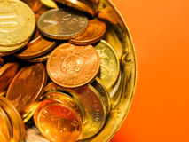 Golden copper and silver coins in a cup with orange background Stock Images