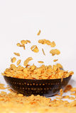 Golden cornflakes falling in a bowl - isolated Stock Image