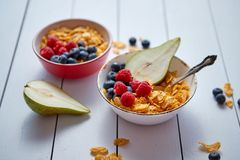 Golden cornflakes with fresh fruits of raspberries, blueberries and pear in ceramic bowl. Golden cornflakes with fresh fruits of raspberries, blueberries and royalty free stock images