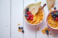 Golden cornflakes with fresh fruits of raspberries, blueberries and pear in ceramic bowl. Golden cornflakes with fresh fruits of raspberries, blueberries and stock images
