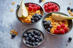 Golden cornflakes with fresh fruits of raspberries, blueberries and pear in ceramic bowl. Healthy breakfast for two is served. Golden cornflakes with fresh royalty free stock photography