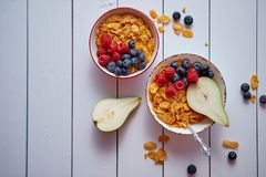 Golden cornflakes with fresh fruits of raspberries, blueberries and pear in ceramic bowl. Golden cornflakes with fresh fruits of raspberries, blueberries and royalty free stock photos