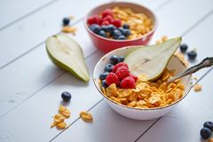 Golden cornflakes with fresh fruits of raspberries, blueberries and pear in ceramic bowl stock image