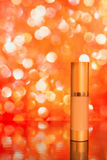 Golden cosmetic tube of tinted cream on red blurred background w. Golden cosmetic tube of tinted cream on bright red blurred background with reflection. Copy Royalty Free Stock Images