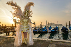 Golden costumed masked woman. In front of gondolas at sunrise in Venice Stock Photos