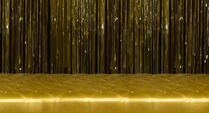 Golden couch with buttons and golden curtains Stock Images