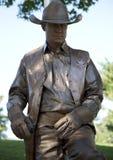 A golden cowboy with gun. Human sculpture, it is Frisco Arts walk in Hall Park , TX USA 2017 stock photography