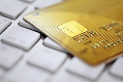 golden credit card on a computer keyboard. Concept o Royalty Free Stock Images