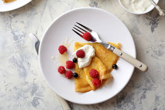 Golden crepe with raspberry and cream Royalty Free Stock Photo