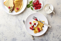 Golden crepe with raspberry on white plate. Food top view Royalty Free Stock Photo