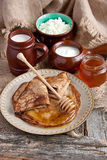 Golden crepes with honey and dairy products Stock Photos