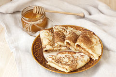 Golden crepes with honey Stock Photography