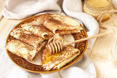 Golden crepes with  honey Stock Photo