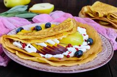 Golden crepes with pieces of peach, pear, cream and grapes on a ceramic plate. On a dark background royalty free stock photo