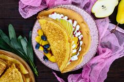 Golden crepes with pieces of peach, pear, cream and grapes. On a ceramic plate on a dark background. Top view royalty free stock photos