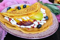 Golden crepes with pieces of peach, pear, cream and grapes. On a ceramic plate on a dark background stock photo