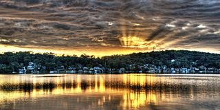 Golden Crepuscular sunrise water reflections. An inspirational colourful panoramic orange and gold sunrise photo with vivid sun rays and bold cloudscape water Stock Photo
