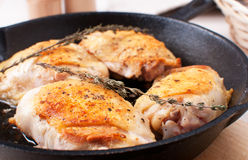 Golden crisp chicken thighs with herbs and spices Stock Photo