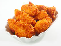Golden crisp fried chicken nuggets. Golden crisp fried crumbed chicken nuggets served in a fluted dish as an appetizer or finger food on a white background stock photos