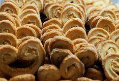 Golden and crisp palmier cookies. Horizontal shot of back lit tray with baked pastry sweets with sugar in a palm shape royalty free stock image