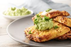 Golden crisp rosti from cauliflowerand parmesan cheese with avoc. Ado dips and parsley garnish on a gray plate, close-up, selective focus, narrow depth of field Royalty Free Stock Image