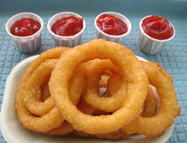 Golden crispy onion rings. A pile of onion rings onan environmentally friendly tray with four containers of ketchup Royalty Free Stock Photos