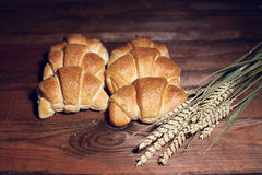 Golden croissants and wheat. Several fresh, golden croissants and whole stalks of wheat sit on the edge of a dark pine table Stock Photo