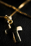 Golden cross. Golden jewelry cross with necklace on black ground Stock Photo