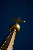 Golden cross against a blue sky. Royalty Free Stock Photos