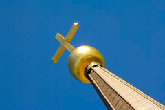 Golden cross against a blue sky. Stock Photos