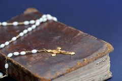 Golden cross and ancient Bible against blue background. Closeup of an old golden cross necklace on an ancient book (Holy Bible Stock Photography