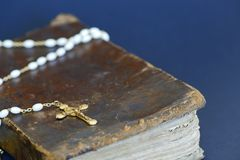 Golden cross and ancient Bible. Closeup of an old golden cross and an ancient Bible against blue background Stock Images