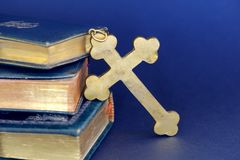 Golden cross and ancient Bibles. Religious items: old golden cross and ancient books (Holy Bibles) against blue background Royalty Free Stock Images