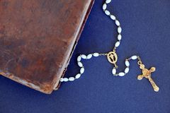 Golden cross and ancient Holy Bible against blue background. Corner of old book (Holy Bible) and a golden cross necklace with white beads Stock Photos