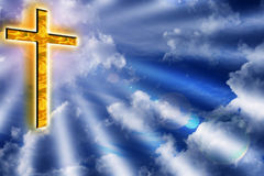 Golden cross in cloudy blue sky Stock Photos
