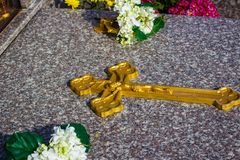 Golden Cross display on the tombstone, flower display for remembrance royalty free stock photo
