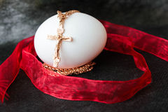 White Easter egg and golden cross with red ribbon royalty free stock photo