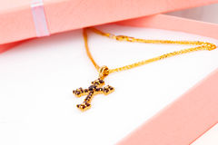 Golden Cross with garnets. In packaged royalty free stock image