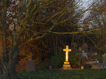 Golden cross. The golden light of the setting sun shining upon a gravestone cross in a cemetery in England, United Kingdom stock photos