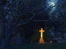 Golden cross. Golden light shining upon a gravestone cross in a cemetery in England, United Kingdom stock photos