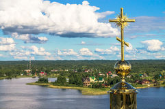 Golden cross on the main dome of the Epiphany Cathedral, Nilov Monastery, Tver region. In the background you can see the nearest shore of the lake Seliger Stock Photography
