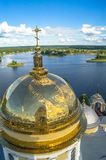 Golden cross on the main dome of the Epiphany Cathedral, Nilov Monastery, Tver region. In the background you can see the nearest shore of the lake Seliger Royalty Free Stock Photos