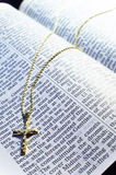 Golden Cross necklace on an open Bible Royalty Free Stock Photo