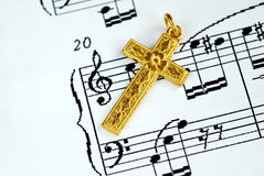 A golden cross on the top of a music sheet Stock Images