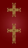 Golden cross. Two gold knitted a cross on a red background Royalty Free Stock Image