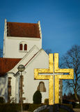 Golden cross at village church Stock Photo