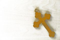 Golden cross on wooden background. Ancient golden cross on white wooden background Stock Photography