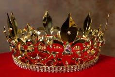 Golden crown on red velvet. Medieval golden king's crown on red velvet pillow Royalty Free Stock Image