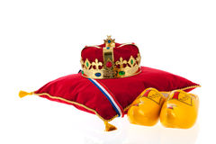 Golden crown on velvet pillow with wooden shoes. Golden crown on red velvet pillow for coronation in Holland with pair of wooden shoes Stock Images